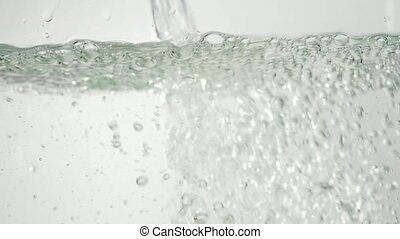 Water pouring on surface and splashing. Bubbles rising in...