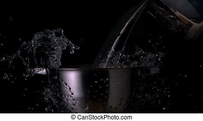 Water pouring over colander on black background in slow...