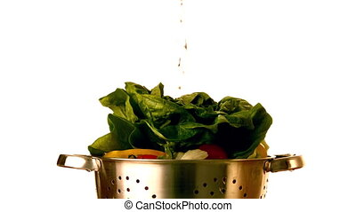 Water pouring over salad in colander in slow motion