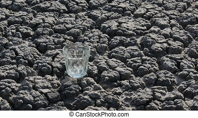 Water pouring to glass at dry ground