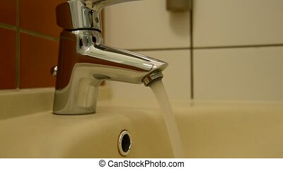 Water pours from the faucet in  kitchen