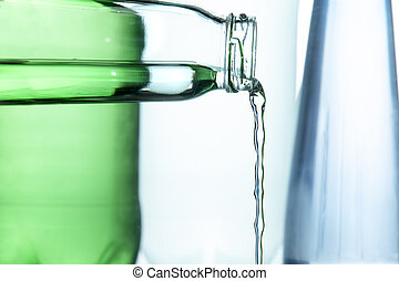 Water pours from the neck of a glass bottle
