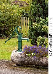 water pump - hand pump water feature in a summer garden