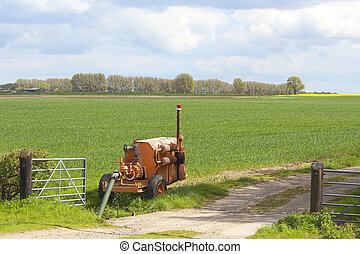 water pump - agricultural landscape with an orange water...