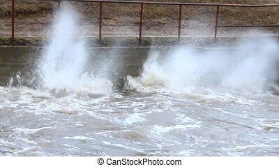 Water raging on dam during spring flood. Flooding river during melting of snow