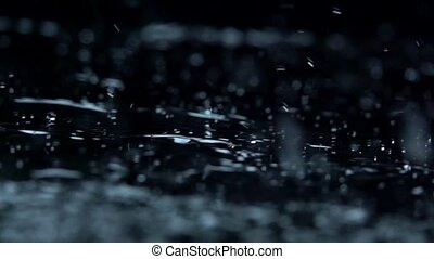 Water rain drops on Black Background. Slow motion. Macro.