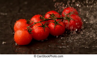 Water raining on cherry tomatoes in slow motion
