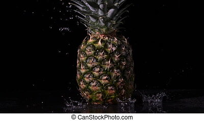 Water raining on pineapple on black background in slow...