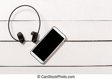 water resistant Headphones with Smartphone on wooden background