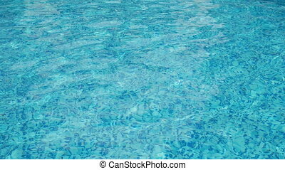 Water ripples on blue tiled swimming pool background. View...