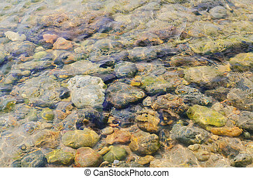 water ripples on the shallow. Sea underwater pebbles abstract background