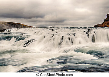 Water run down waterfall in Iceland on mountain landscape on...