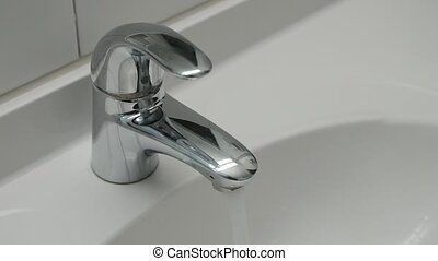 Water running continuously from water tap. Close-up.