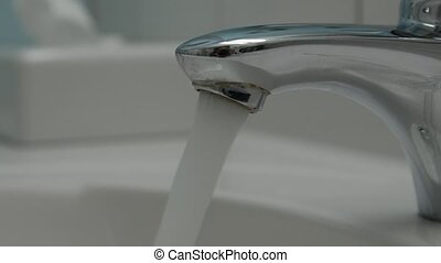 Water running continuously from water tap. - Water running...