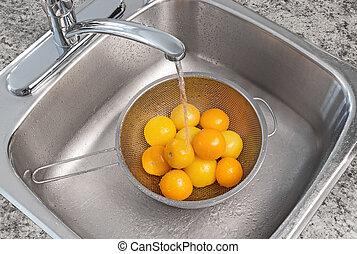 Washing yellow tomatoes