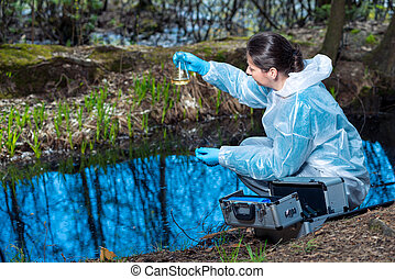water sample from a forest river in a flask in the hands of an ecologist biologist