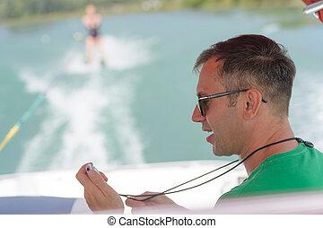 water ski coach monioring female learner
