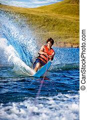 Water Skiing - A man water skiing on a lake