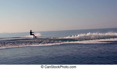 Water Skiing At Sunrise - Young Man Wakeboarding Jump On...