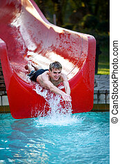 water slide - Young male teenager having fun on a water...