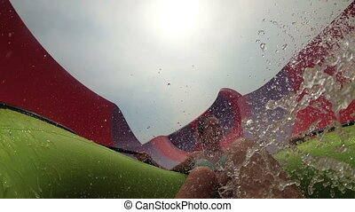 Water slides pov. Guy with girl on the inflatable circle descends from the water slides. Slow Motion