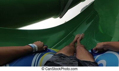Water slides pov. Guy with girl on the inflatable circle descends from the water slides. Thailand