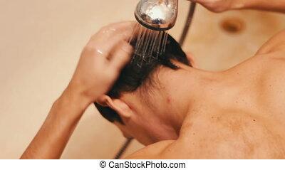 Water splash hitting on man's head.Young man washing hair...