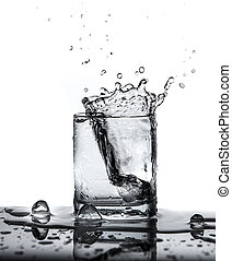 water splash with ice in glass isolated on white background