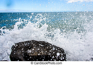 Water splashes on rock with the ocean in the background