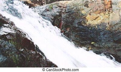 Water splashing against rocks (slow motion)
