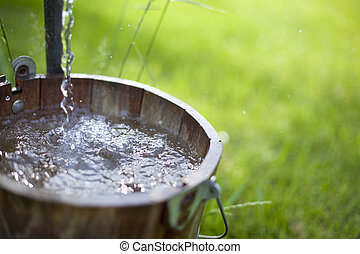 Clean, fresh well water splashes in a bucket in the country.