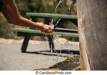 Water splashing in girls hands in the rural area