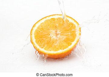 Water splashing on half of ripe, juicy orange.