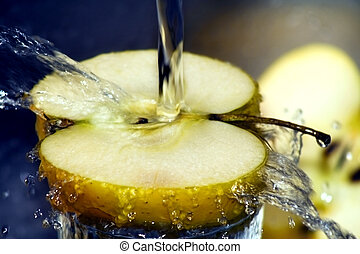 Water splashing over sliced apple