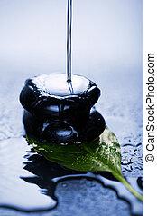water splashing over zen stone on leaf