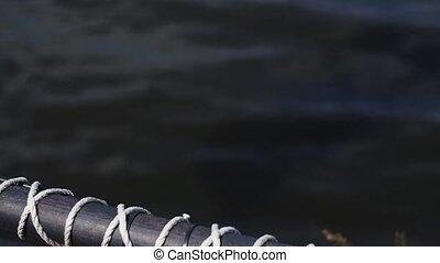 Water spray from iron valve on black fence at coast. Summer...