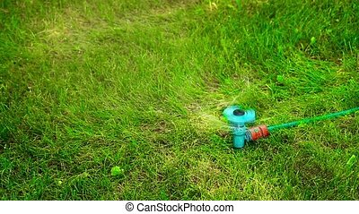 Water sprayer on the lawn in motion on a hot summer day HD
