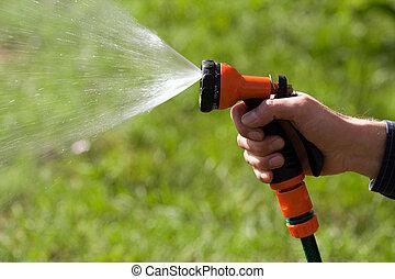 Water sprinkler in the sun - orange water sprinkler watering...
