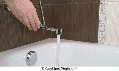 Water stream flows from the water tap into the tub - The...