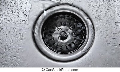 Water stream going down the drain. Streaming water in sink. ...