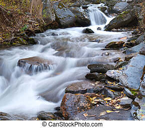 Rapid river stream and large stones.
