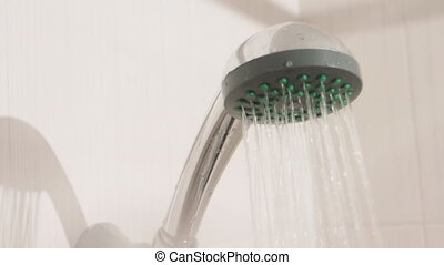 Water streams. Metal shower head in white bathroom. Working plumbing equipment.