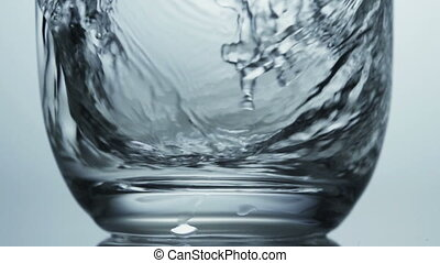 Water swirling around a glass as it is poured in - Close up...