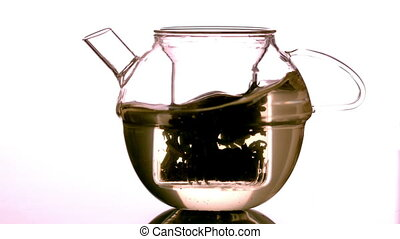 Water swirling around loose tea in teapot in slow motion