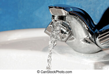 Water tap with flowing water. Selective focus, shallow depth of field