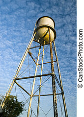 An old water tower framed against a beautiful blue sky filled with white puffy clouds.