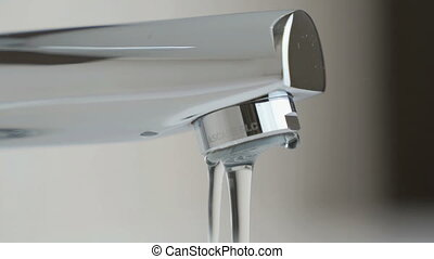 Water under weak pressure flows from a water tap - The water...