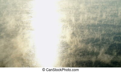 Water vapor on surface of cold icy water in river at sunny...