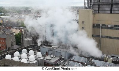 water vapour rising up to cityscape from factory