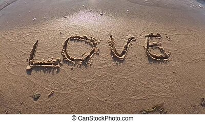 Water washes away the word love in the sand